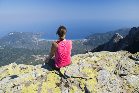 Fit young girl sitting on a mountain peak enjoying the view from up high of the village and the sea bellow. photo