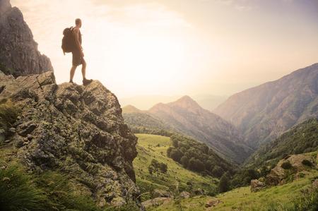 Zdrowy młody człowiek stojący na szczycie skały wysoko w górach, podziwiając piękno przyrody w świetle poranka.