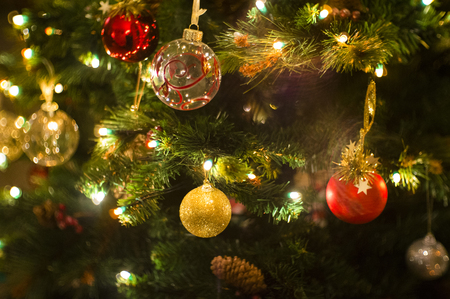 Christmas tree decorated with lights, balls, bells and other ornaments. photo
