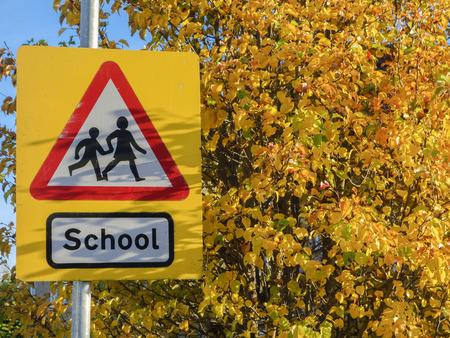 ni�os caminando: Escuela de se�al de advertencia en el fondo amarillo de las hojas de oto�o.