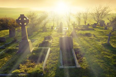 Niebiańskie światło świeci się na starym cmentarzu w Anglii, Wielkiej Brytanii.