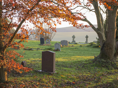 The golden light of the setting sun shining upon a graveyard in England, United Kingdom.