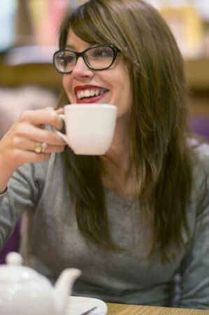 cosy: Beautiful young woman enjoying a hot drink with friends in a cosy cafe.