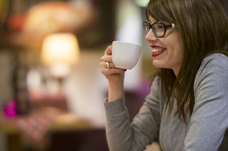 Beautiful young woman enjoying a hot drink with friends in a cosy cafe.