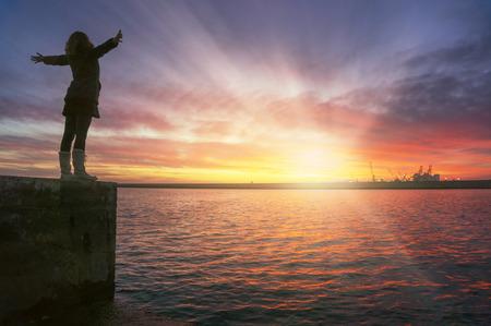 喜びおよび満足、夢のような夕日海の上で空気を彼女の腕を持つ若い女性。