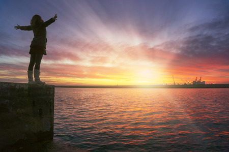 Young woman with her arms up in the air with joy and contentment watching the dreamy sunset over the sea.