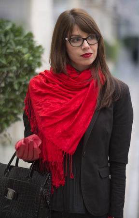 Beautiful young woman with in elegant black clothes and red scarf walking in a shopping center. Stock Photo