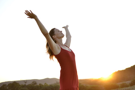 Happy young woman with a red dress praising the beauty of life under the rays of the setting sun. Stock Photo