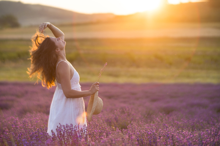 Beautiful young woman wearing a white dress playing with he long hair in a middle of a lavender field under the golden light of sunset.