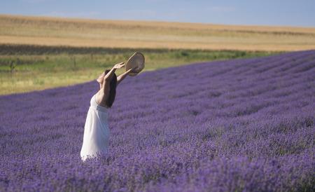 Hermosa mujer joven con un vestido blanco que celebra la belleza de la vida de pie en medio de un campo de lavanda en flor.