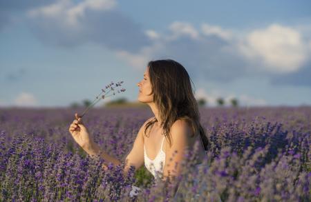 Hermosa mujer joven que sostiene un manojo de flores de lavanda que disfrutan de su fragancia en el medio de un campo de lavanda al atardecer.