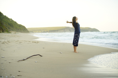 desolate: Beautiful young woman with her arms up enjoying the sense of freedom on a desolate beach.