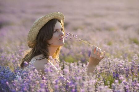 campo de flores: Hermosa mujer joven que llevaba un sombrero de paja, que sostiene un manojo de flores de lavanda, gozando de su fragancia sentado en el medio de un campo de lavanda al atardecer.
