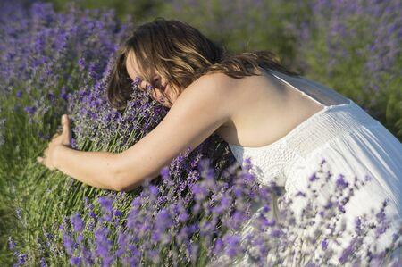 olfato: Hermosa mujer joven con un vestido blanco que abraza a un arbusto de la lavanda disfrutando de la fragancia. Foto de archivo