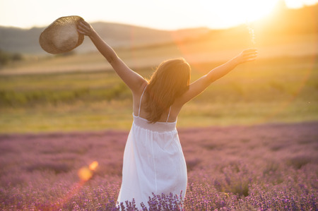 Beautiful young woman with a white dress and a straw hat standing in the middle of a lavender field at in the golden light of the sunset praising the beauty of life.