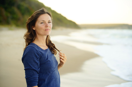 tranquility: Beautiful young woman looking in the distance, enjoying a moment of quiet happiness and tranquility.