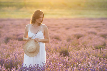 Belle jeune femme vêtue d'une robe blanche debout dans un moment de paix et de sérénité dans un milieu d'un champ de lavande sous la lumière dorée du soleil couchant.