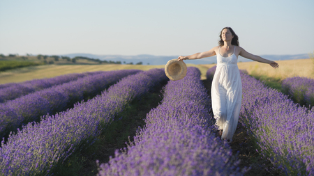 woman in field: Beautiful young woman wearing a white dress walking in the middle of a lavender field in bloom. Stock Photo