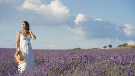 Mooie jonge vrouw draagt een witte jurk staat in het midden van een veld lavendel in bloei.