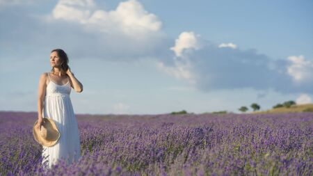 woman in field: Beautiful young woman wearing a white dress standing in a middle of a lavender field in bloom.