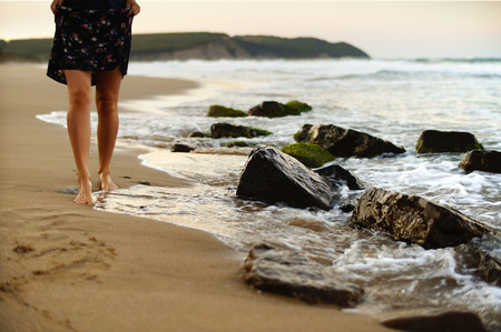 sandy beach: Female legs walking on the beach on a warm summer evening.