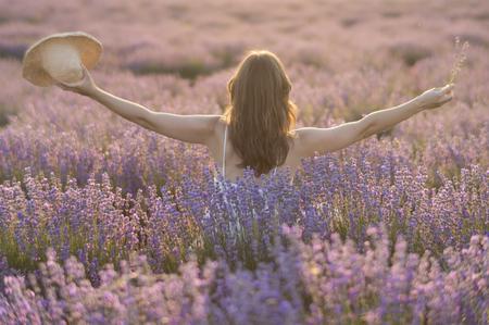 Belle jeune femme avec une robe blanche et un chapeau de paille debout au milieu d'un champ de lavande, dans la lumière dorée du soleil couchant louant la beauté de la vie.