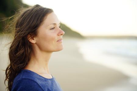 ser humano: Hermosa mujer joven que mira en la distancia, disfrutando de un momento de tranquila felicidad y tranquilidad.