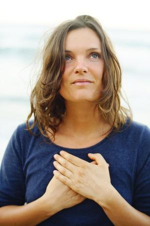Hermosa mujer joven con las manos en su corazón en una oración silenciosa y agradecimiento. Foto de archivo