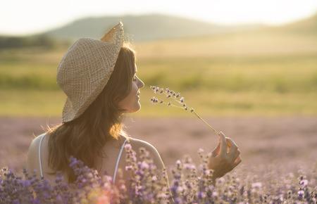 ラベンダーの花の束を持って、夕日の光の中でラベンダー畑の真ん中にその香りを楽しんでいる麦藁帽子の美しい若い女性。