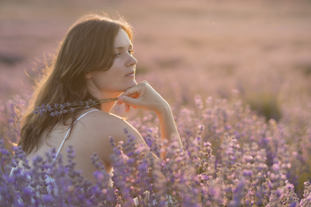 Beautiful young woman holding a bunch of lavender flowers enjoying their fragrance in the middle of a lanvender field at sunset. Stock Photo