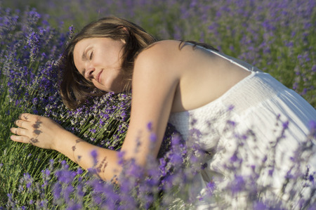 lavender bushes: Beautiful young woman with a white dress hugging a lavender bush enjoying the fragrance.