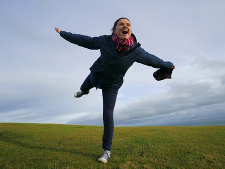 joyfully: Young woman joyfully playing with the strong wind on top of a hill. Stock Photo