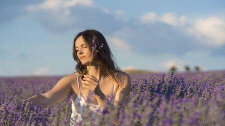 beautiful flowers: Beautiful young woman holding picking lavender flowers in the middle of a lavender field at sunset. Stock Photo