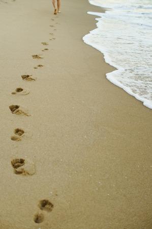 Female legs leaving footprints on the sandy beach.