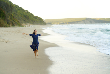 Beautiful young woman with her arms up running on and enjoying the sense of freedom on a desolate beach. 版權商用圖片