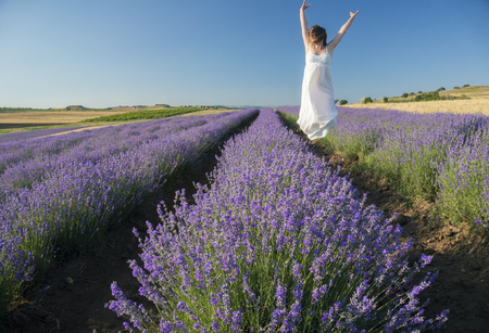 Beautiful young woman wearing a white dress jumping with joy in the middle of a lavender field in bloom. Stock Photo
