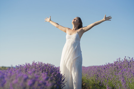 exaltation: Beautiful young woman wearing a white dress celebrating the beauty of life standing in the middle of a lavender field in bloom.