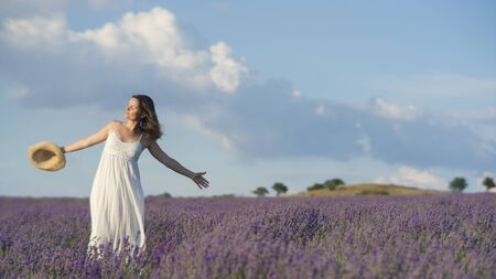 Beautiful young woman wearing a white dress celebrating the beauty of life standing in the middle of a lavender field in bloom.