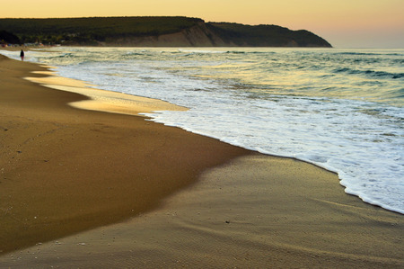 distance: Person Walking in the distance on wild sandy beach under the golden light of a summer evening. Stock Photo