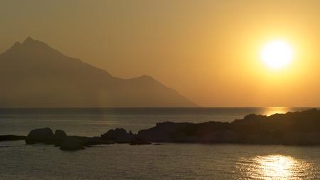 The amazing silhouette of mount Athos rising from the Aegean sea and symbol of Greek orthodox Christianity at sunrise.