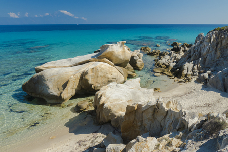 Amazing rock formations surrounding a little wild beach at the coast of Sythonia overlooking Mount Athos.