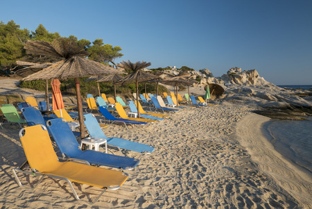 Colorful loungers and reed umbrellas on a sunny morning on the coast of Chalkidiki