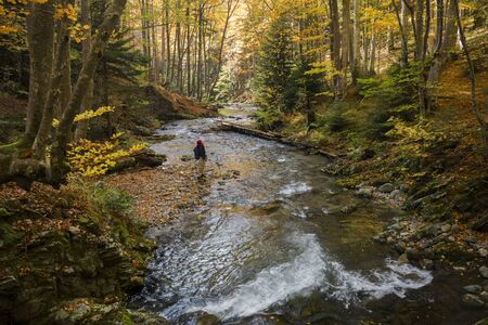Young adventurous woman exploring the natural wilderness in autumn.