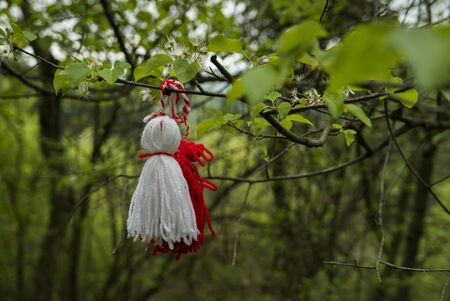 Martenitsa tied to a freshly green branch in spring.
