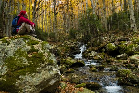 Young woman hiker resting on a big rock in the forest by a stream enjoying the peace and beauty of autumn. 版權商用圖片