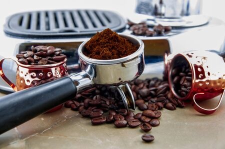 Freshly ground coffee in espresso lever during coffee preparation. In the background a coffee machine, around spilled coffee beans and metal cups. Stockfoto