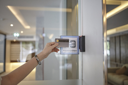 Electronic sensor door- young woman holding a key card