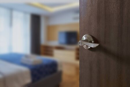 Hotel room , Condominium or apartment doorway with open door in front of blur bedroom background Banque d'images
