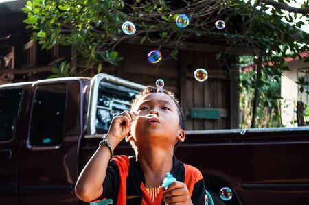 Cute little boy is blowing a soap bubbles photo