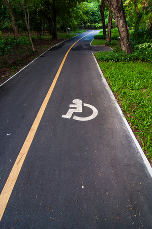 wheelchair users: Road way cyclists and wheelchair in the garden,Thailand